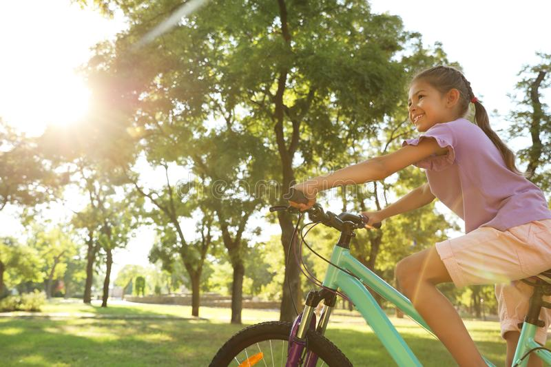 Happy little girl riding bicycle stock images