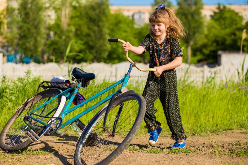 Happy little girl riding big bicycle in park royalty free stock images