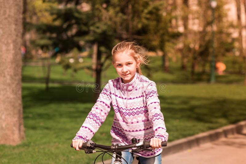 Happy little girl riding a bike stock photography