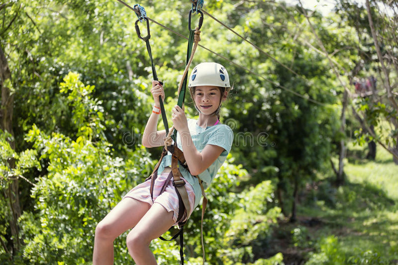 Happy little girl riding a zip line in a lush tropical forest. Happy smiling little girl riding a zip line in a lush tropical forest while on family vacation stock photos