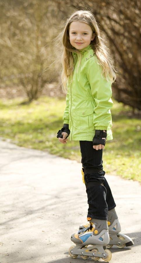 Happy little girl on roller-skates royalty free stock images