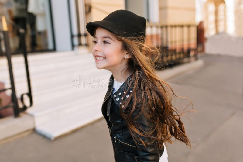 Happy little girl running down the street with dark hair waving and looking away. Portrait of playful brunette girlie stock photo