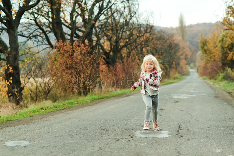 Happy little girl running on the road in autumn time. Stylish fashion child outdoors. Autumn holidays. Childhood, leisure and stock photography