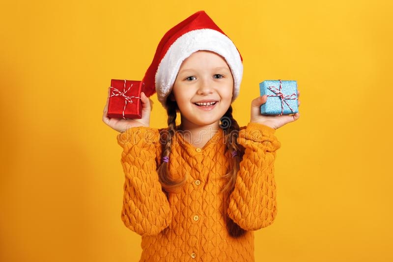 Happy little girl in santa hat holds small boxes with christmas gifts in hands on a yellow background royalty free stock photography