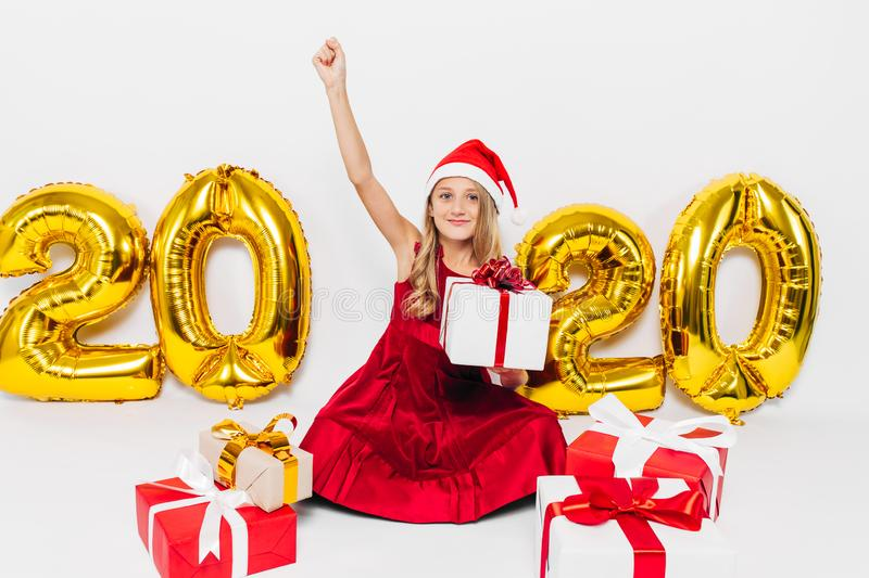 Happy little girl in Santa hat, stylish baby rejoices Christmas gift by showing victory gesture while sitting on white background royalty free stock photo
