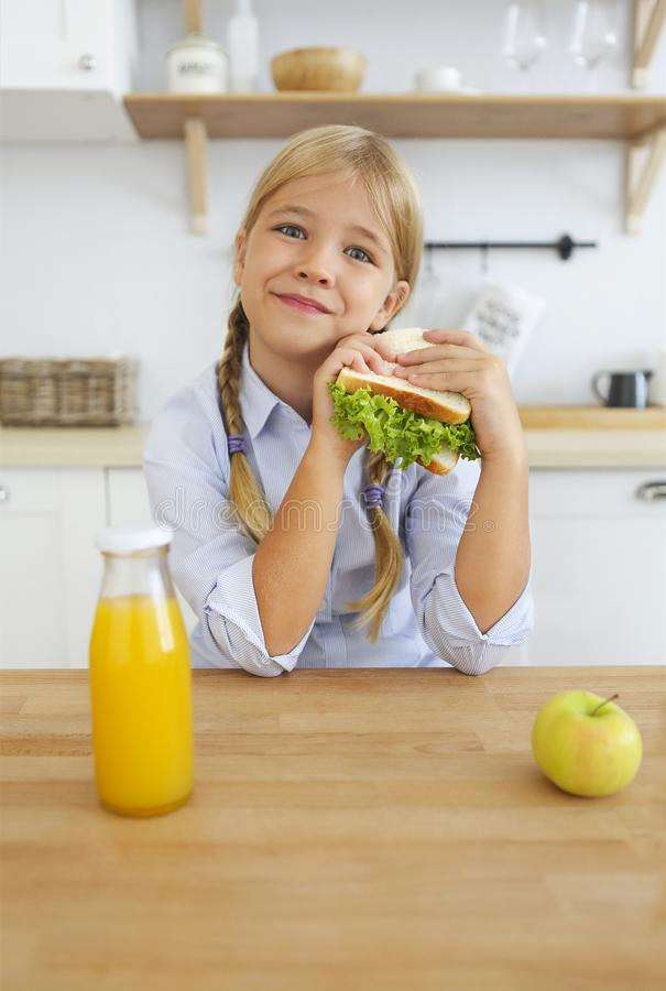 Happy little girl of school age enjoying healthy breakfast eating sandwich and fruits and drinking orange juice sitting at bright stock image