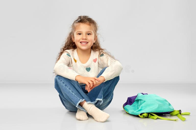 Happy little girl with school bag sitting on floor royalty free stock photography