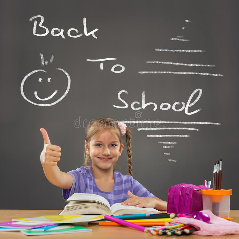 Happy little girl in the school bench shows all okay stock photography