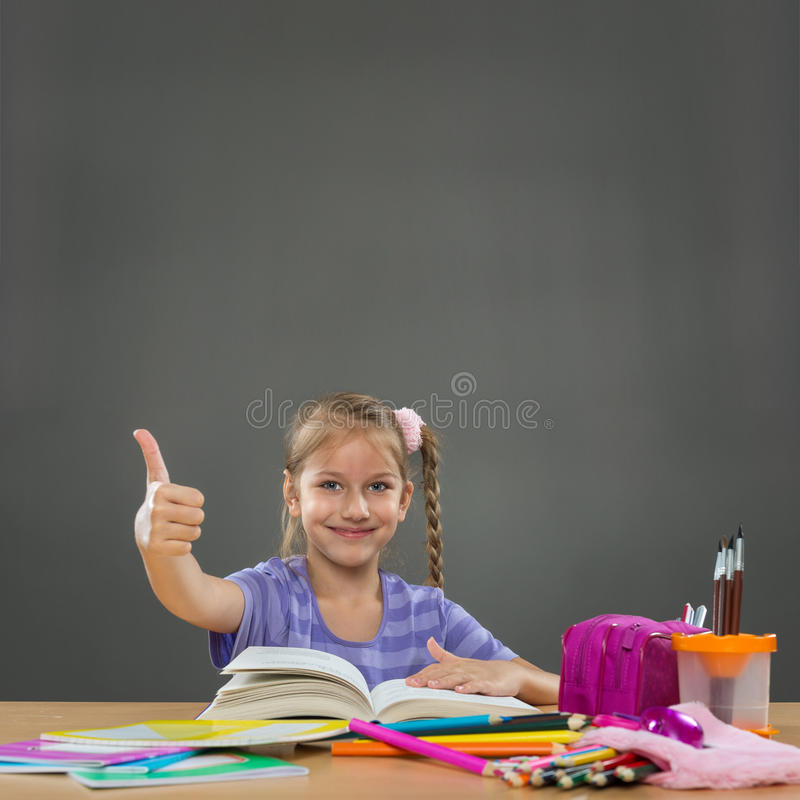 Happy little girl in the school bench shows all okay stock photos