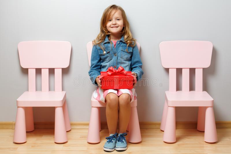 Happy little girl sits on a chair and holds a box with a gift on a background of a gray wall. Empty chairs next to the child. The concept of happiness royalty free stock photos