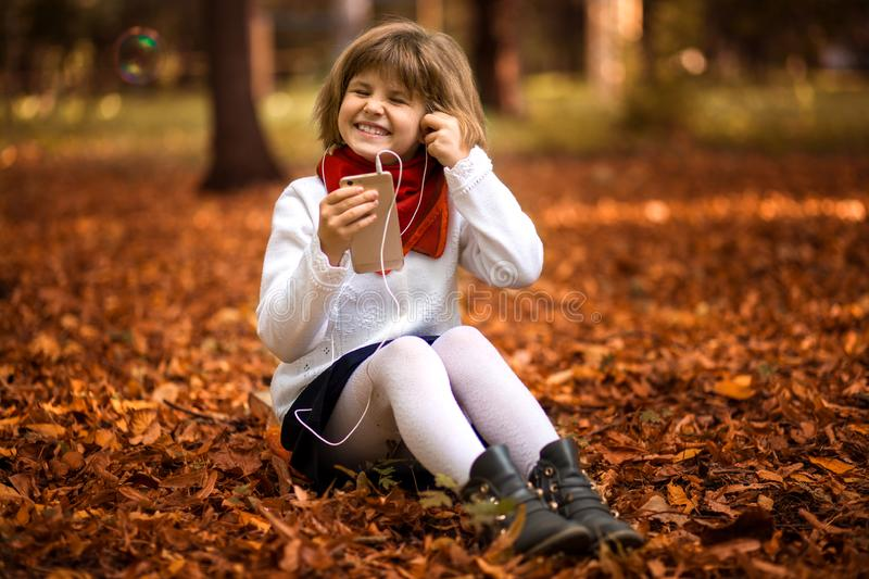 Happy little girl sits on yellow leaves and listens to music in autumn stock photography