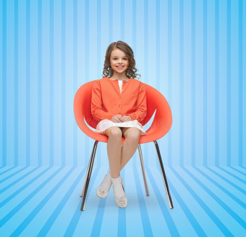 Happy little girl sitting on designer chair stock images
