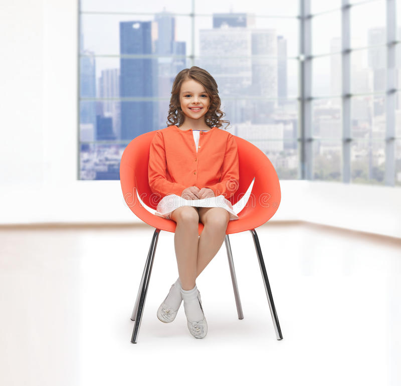 Happy little girl sitting on designer chair royalty free stock photography