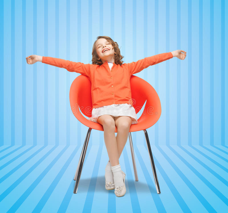 Happy little girl sitting on designer chair royalty free stock photo