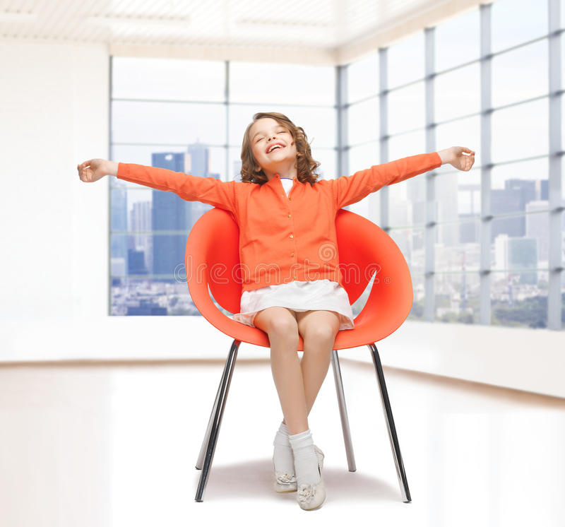 Happy little girl sitting on designer chair stock photography