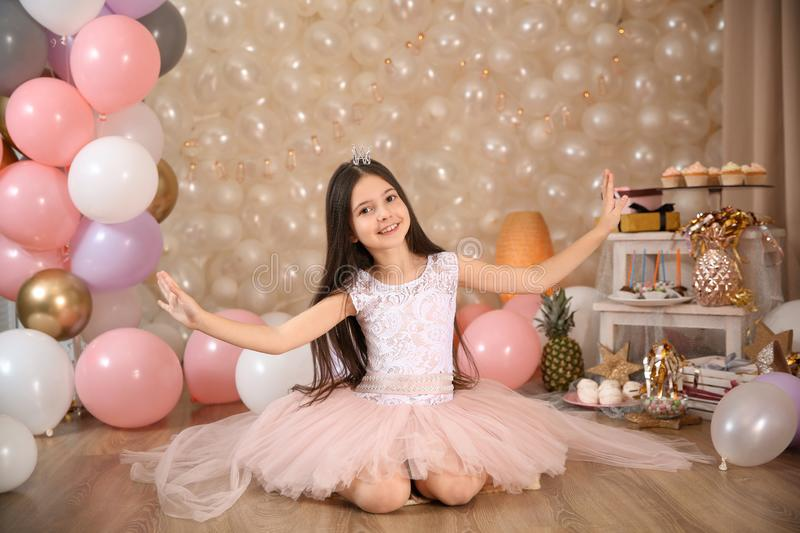 Happy little girl sitting on floor in beautifully decorated room at home stock images