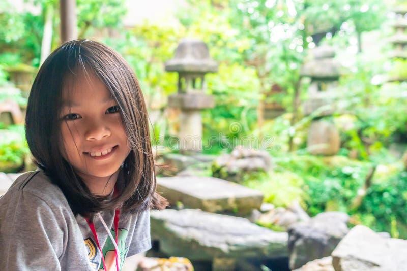 Happy Little girl sitting in Japanese garden stock photo