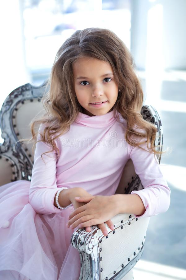 Happy little girl is sitting in the light studio royalty free stock images