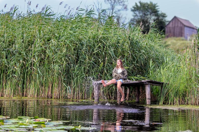 Happy little girl sitting on old wooden jetty surrounded by high green reeds splashing water with her feet at warm summer day. royalty free stock image