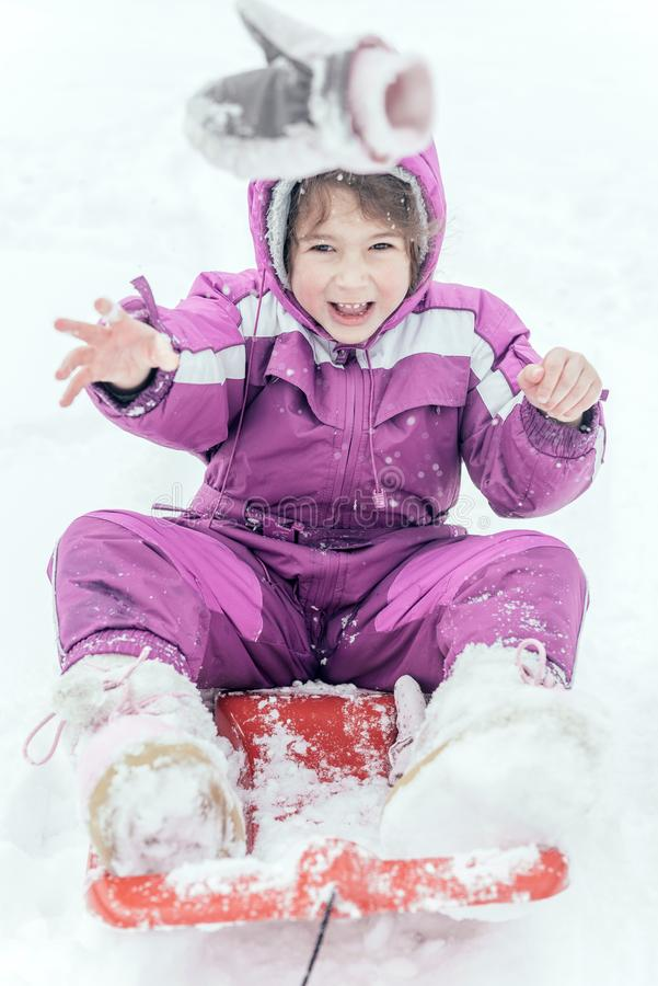 Portrait of the little child outdoor. Happy little girl sitting in a sleigh and glow,selective focus royalty free stock images