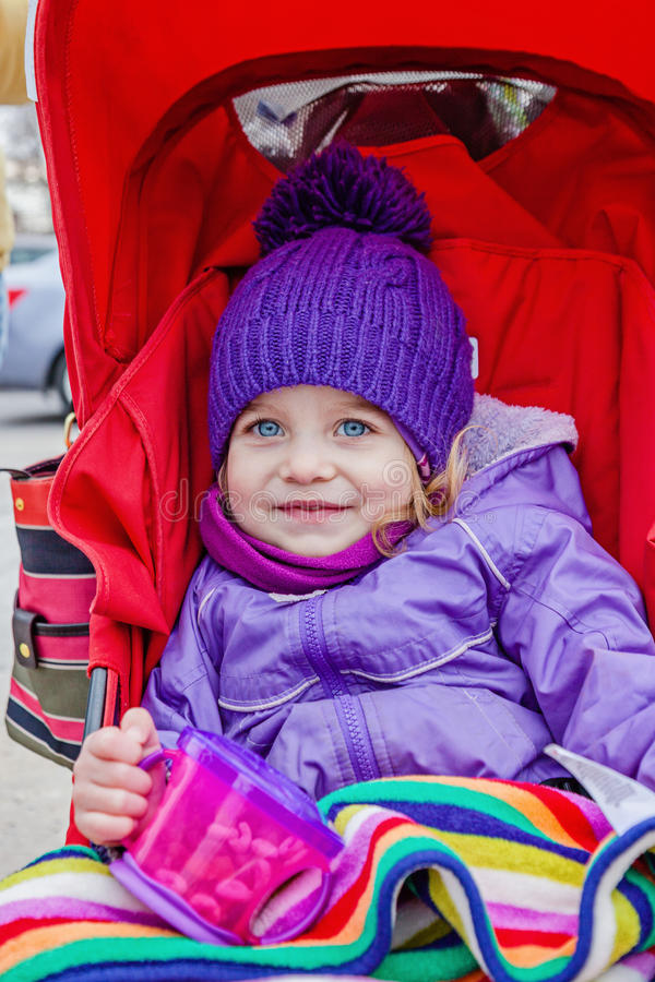Happy little girl sitting in stroller holding a cup with snack. stock photography