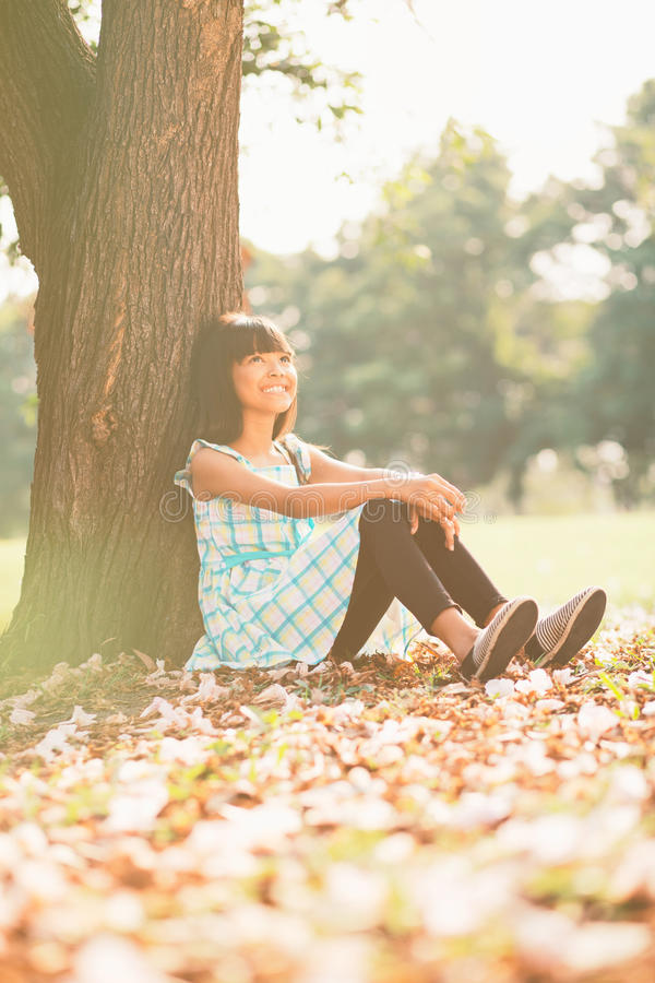 Happy little girl. Sitting unter the tree on a grass in a park royalty free stock photos
