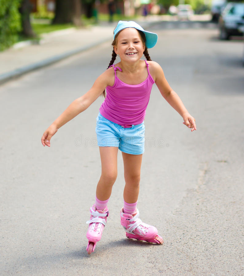 Happy little girl is skating on rollers. Outdoor shoot stock photos