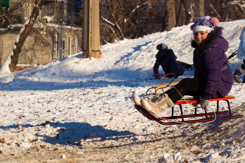 Happy little girl sledding on white snowy snow from a hill royalty free stock photography