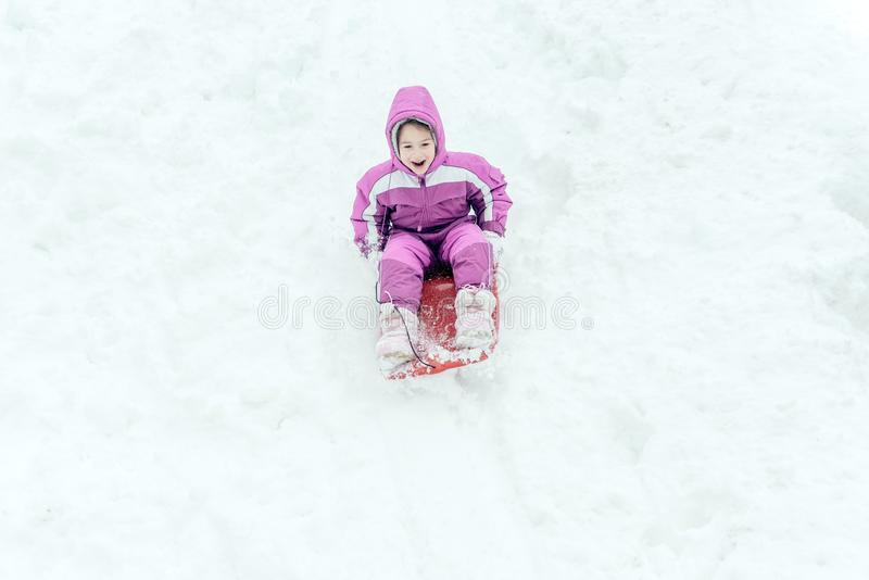Portrait of the little child outdoor. Happy little girl sliding on the sled,selective focus and motion stock photos
