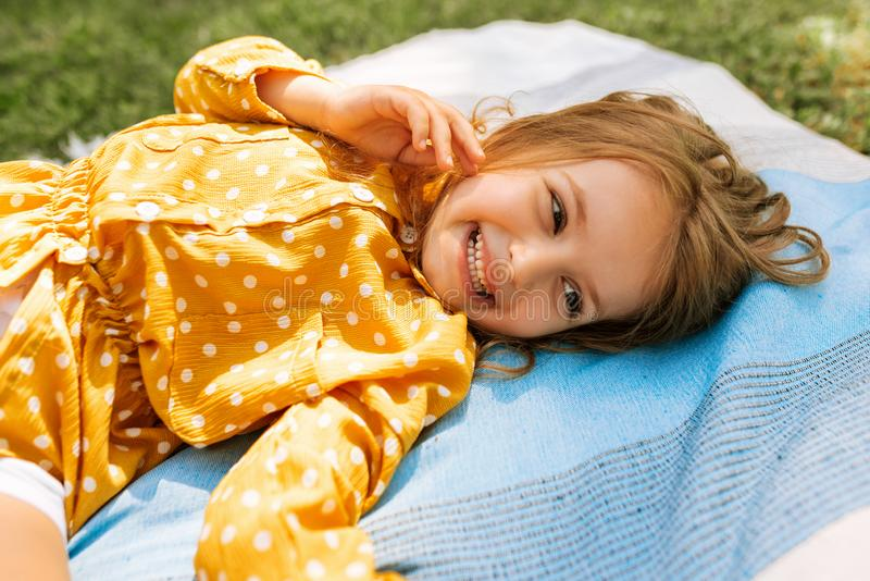 Happy little girl smiling broadly and lying on the blanket at the grass, enjoying summer day outdoors. Adorable child having fun royalty free stock photography