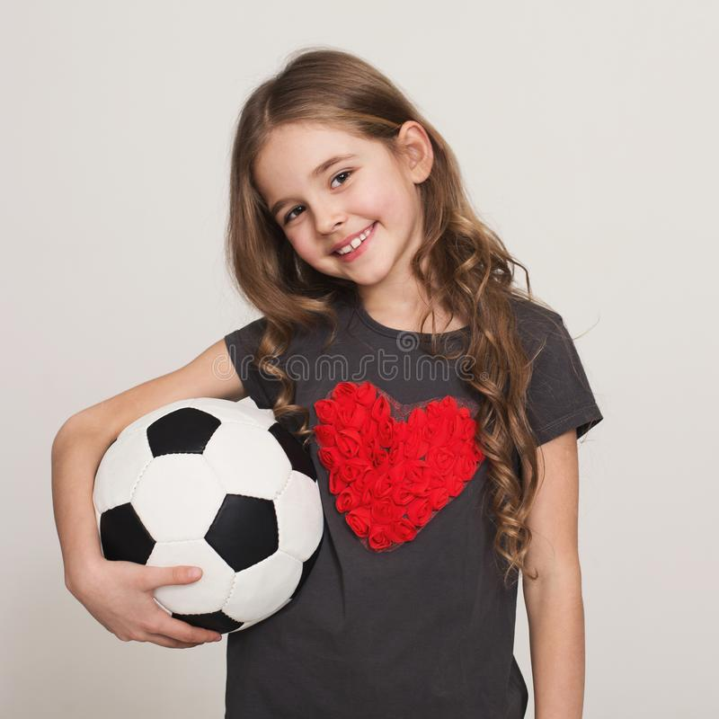 Happy little girl with soccer ball in hands stock photography