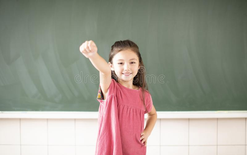 little girl standing against chalkboard background royalty free stock images