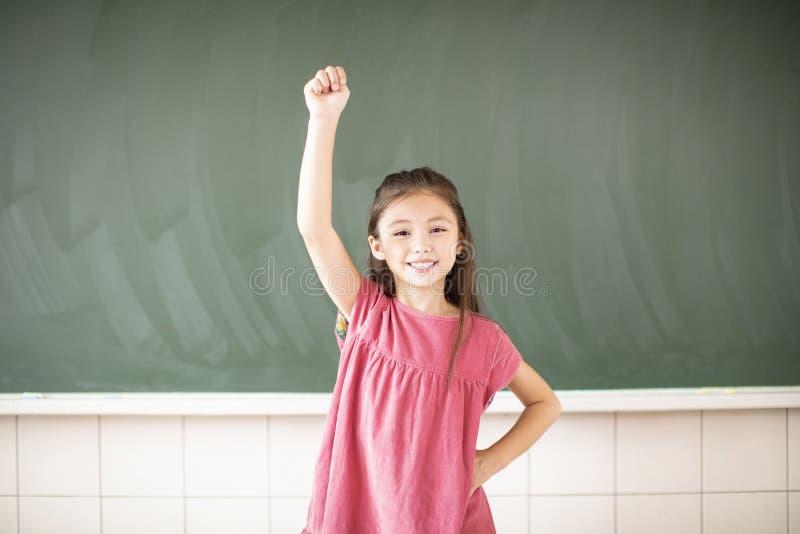 little girl standing against chalkboard background stock image