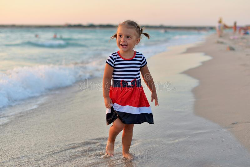 Happy little girl standing barefoot on the wet sand on the beach royalty free stock photo