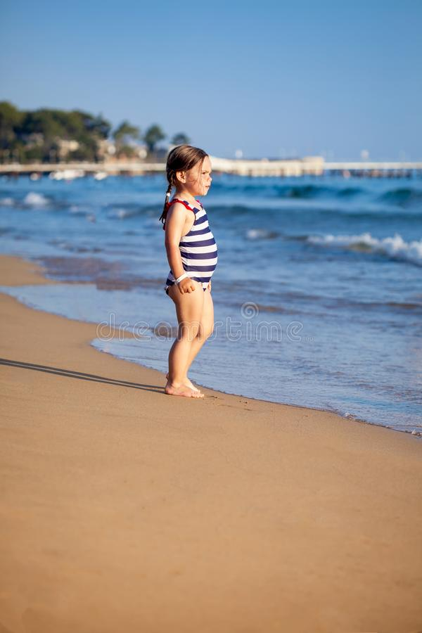 Happy little girl standing on beach near blue royalty free stock image