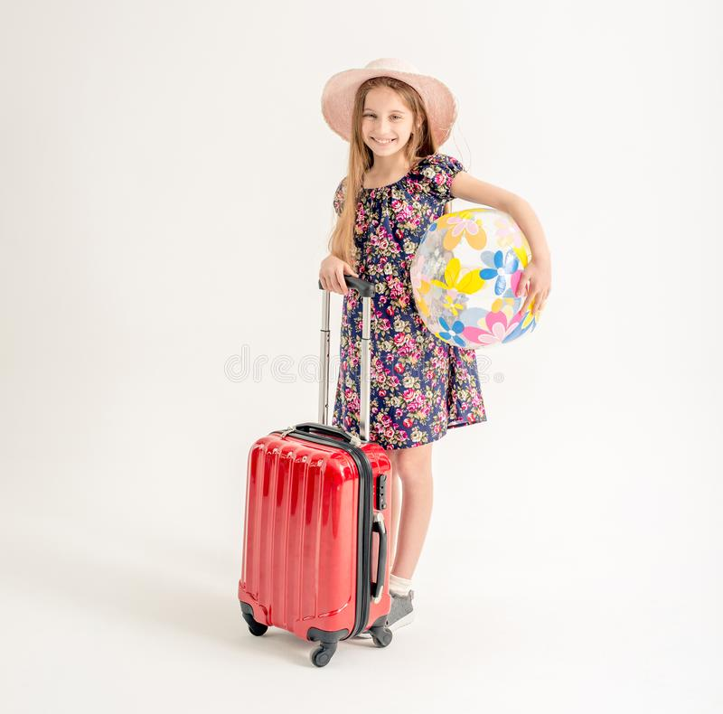 Happy little girl is standing near a suitcase royalty free stock photos