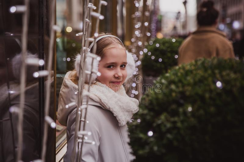 Happy little girl in the street near window with a garland light in winter evening stock photography