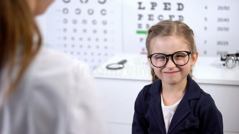 Happy little girl in stylish eyeglasses smiling into camera, happy with eyewear. Stock photo stock image
