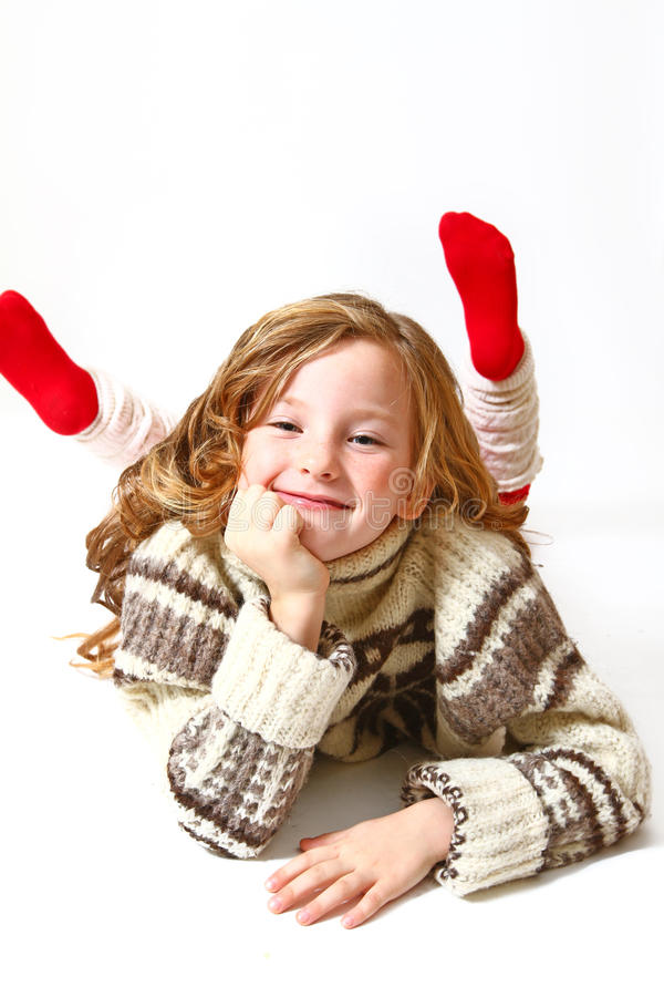 Happy little girl in a sweater lying on a white background stock image