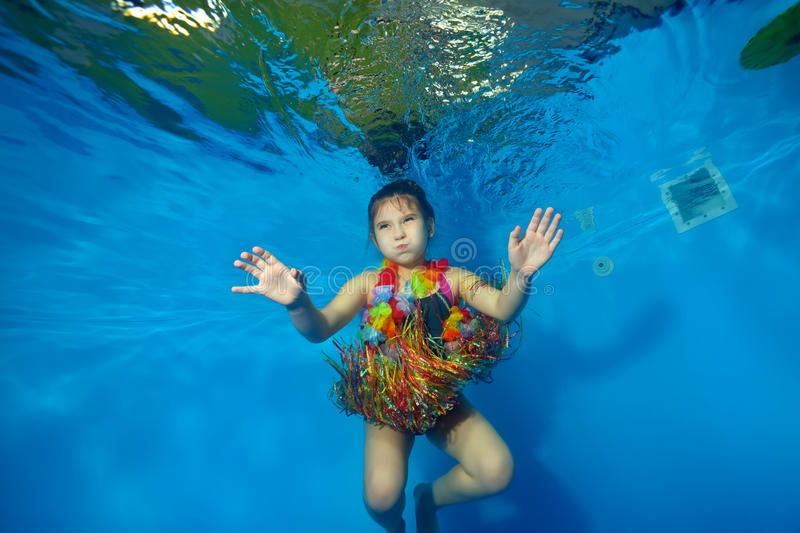Happy little girl swimming and dancing underwater in the pool in costume for carnival on a blue background stock photography