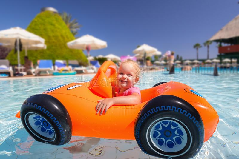 Happy little girl swimming in the inflatable car stock images