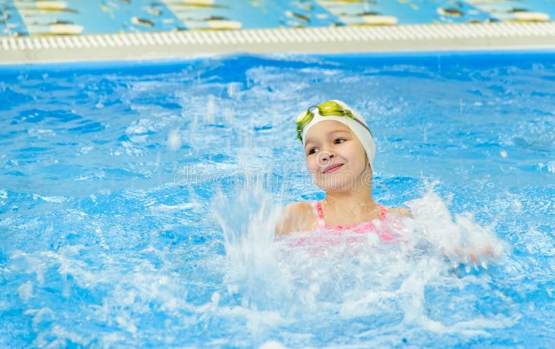 Happy little girl swimming in the pool. Caucasian child is playing fun in the kindergarten pool stock photos