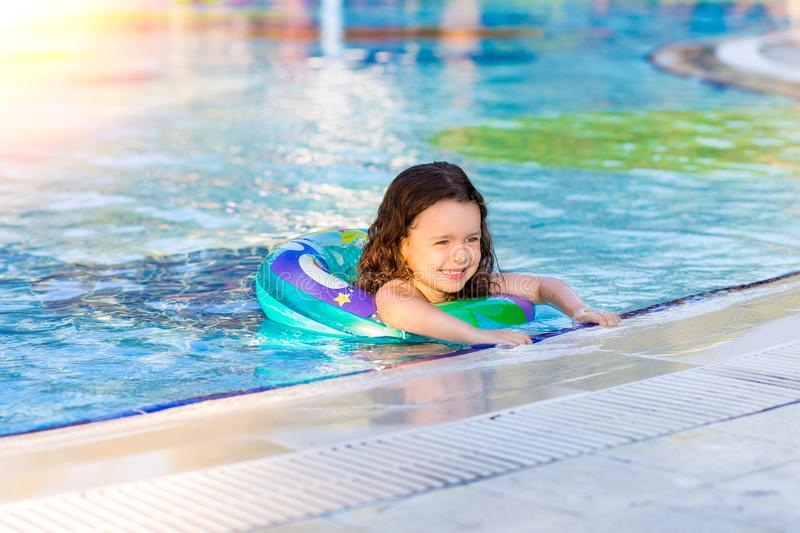 Happy little girl swimming in the pool with inflatable ring on a Sunny summer day. Kids learn to swim. Family vacation royalty free stock photography