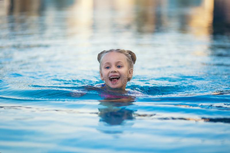 Portrait of cute happy little girl having fun in swimming pool. royalty free stock photography