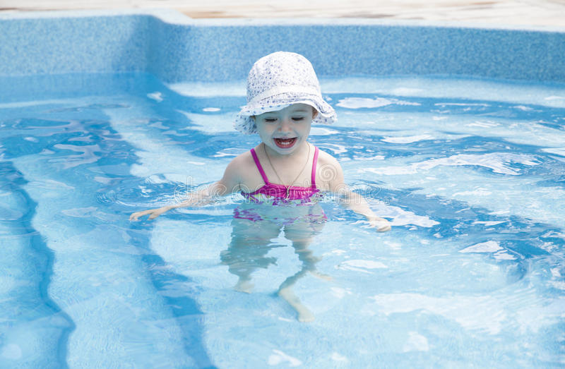 Happy little girl in swimming pool. Portrait of a toddler in swimming pool royalty free stock image