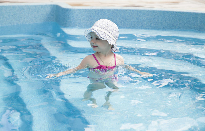 Happy little girl in swimming pool. Portrait of a toddler in swimming pool stock photos