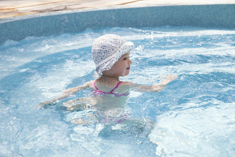 Happy little girl in swimming pool. Portrait of a toddler in swimming pool royalty free stock photo