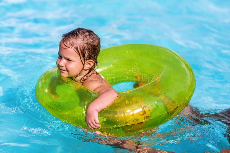 Happy little girl swims in a pool in at green life preserver stock images