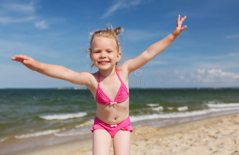 Happy little girl in swimwear having fun on beach. Summer, childhood, vacation and people concept - happy little girl in swimwear having fun on beach stock photos