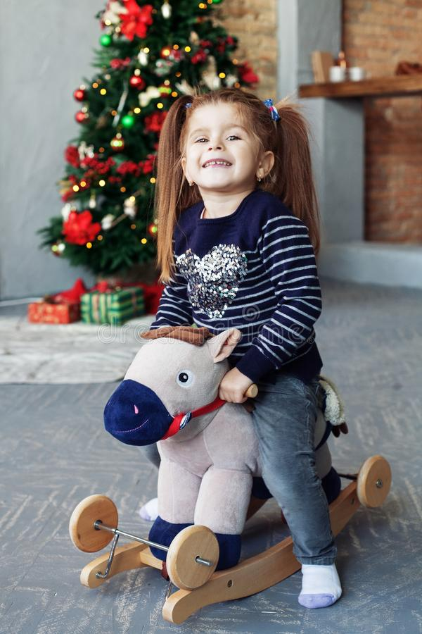 Happy little girl swinging on a horse. The concept of Christmas stock image